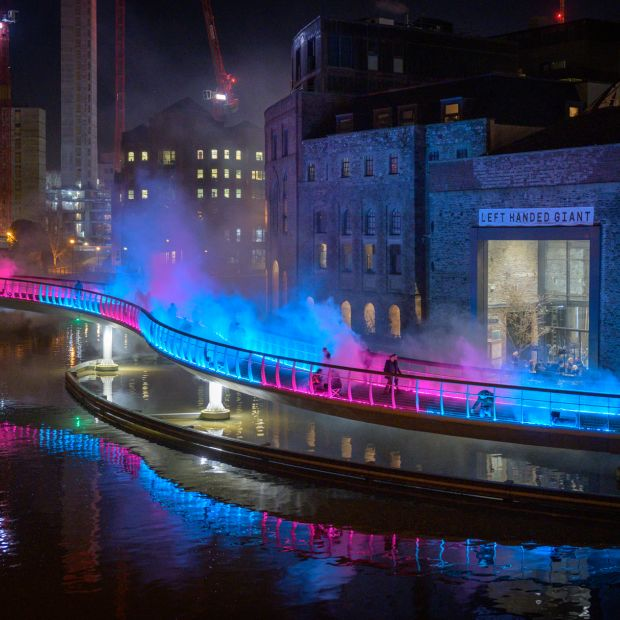A light installation with pink and blue lights on a bridge in bristol