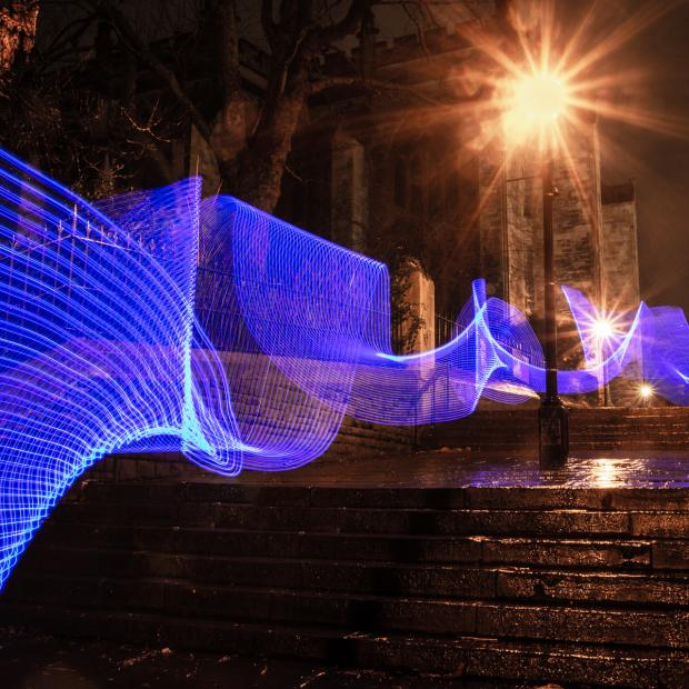 A path of blue light coming down concrete stairs