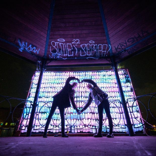 A lit up screen made of milk bottles with two people making a heart shape with their arms